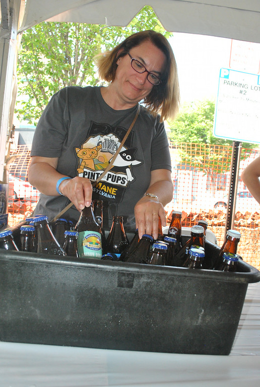 Description of . Kim Feindt gets the beers ready for tasting at Pints for Pups in Phoenixville Aug. 9.