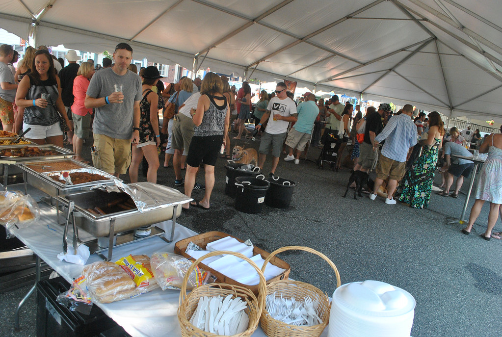 Description of . The crowd at Pints for Pups enjoys the music and samples the beers.